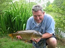 A happy holiday angler as he proudly presents one of many good Carp caught by him at Nineoaks