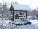 A winter picture showing the snow covered entrance sign