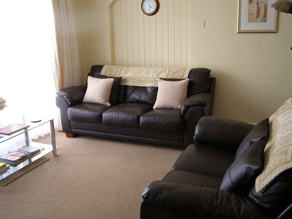 A view of the good sized lounge with leather couches, large TV, freeview and CD for your comfort